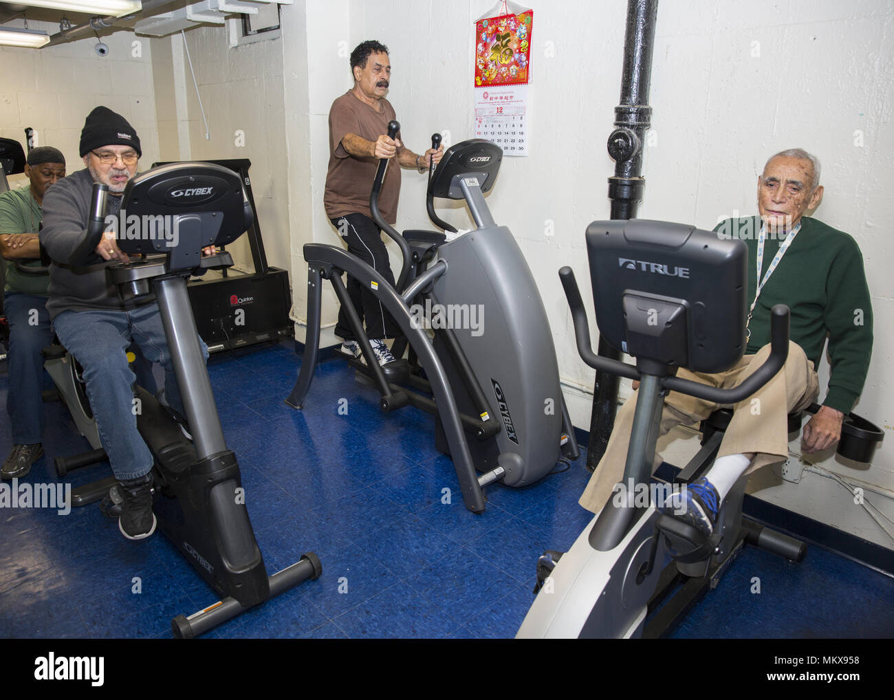 Men keep fit, working out on the exercise machines provided at a senior center on tghe Lower East Side, Manhattan, New York City. - Stock Image