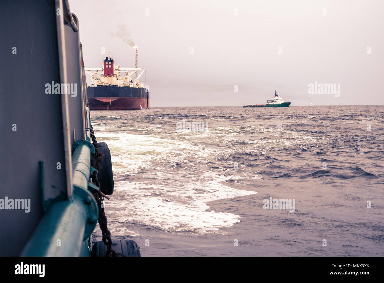 Anchor-handling Tug Supply AHTS vessel at work with FPSO tanker Stock Photo