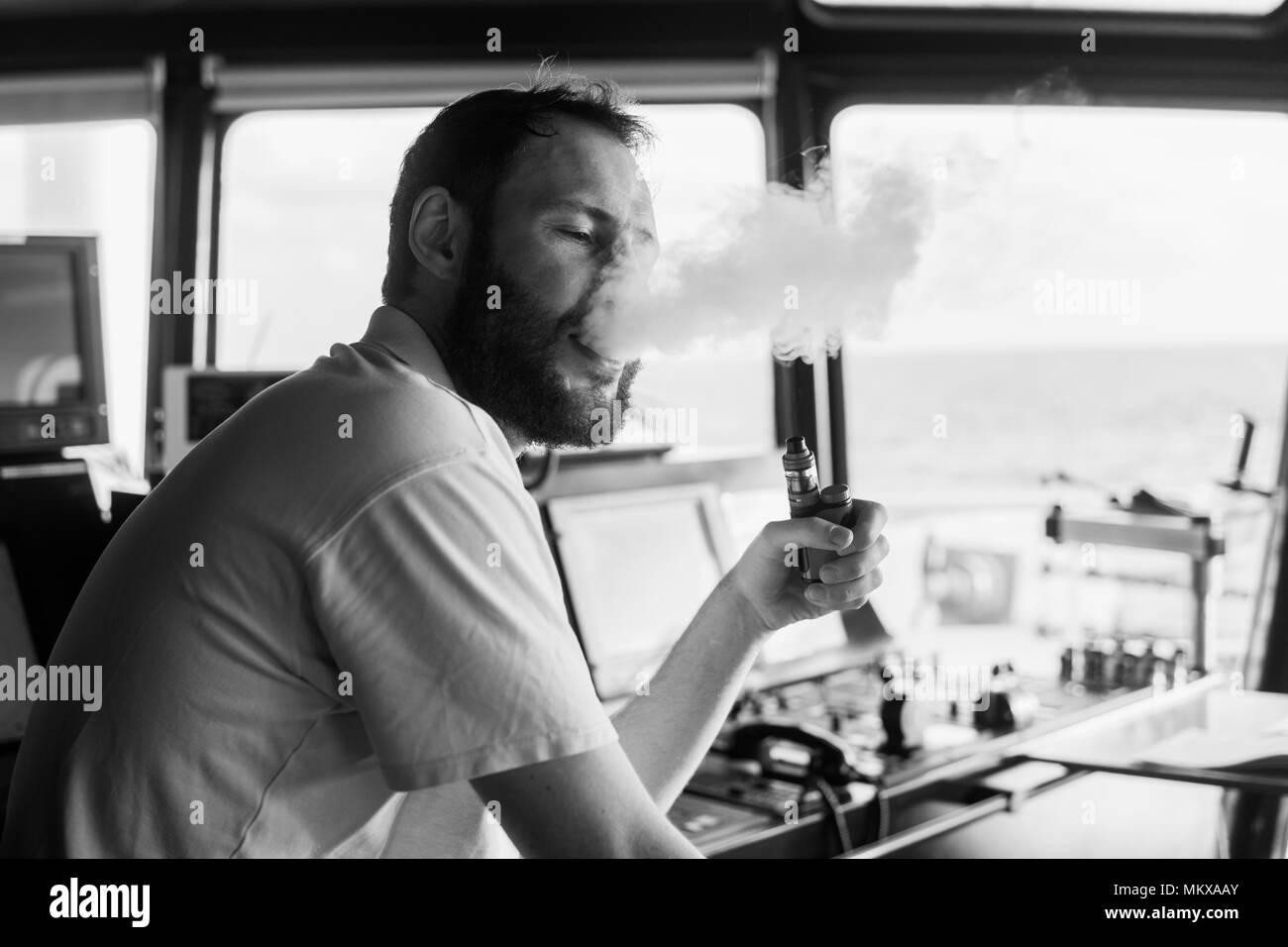 Deck navigation officer smokes a wad on the navigation bridge of yacht - Stock Image