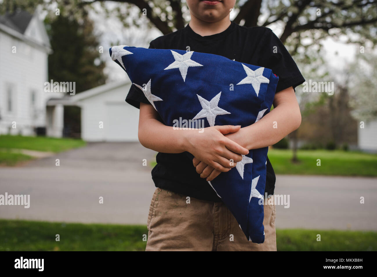 A young boy holding a folded American flag. - Stock Image