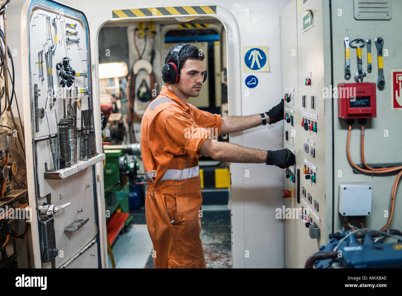 Marine engineer officer controlling vessel engines in engine control room ECR - Stock Image