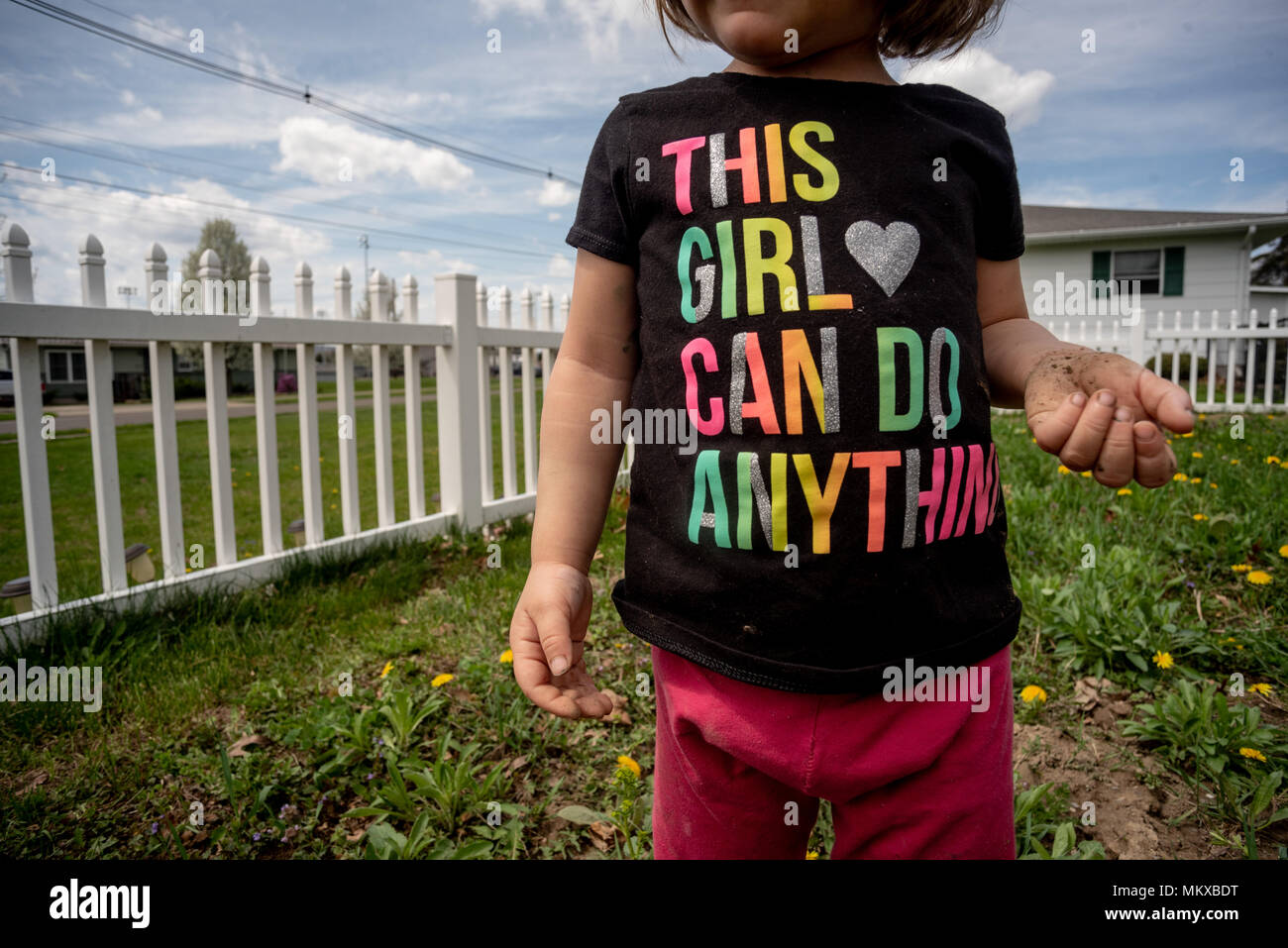 A little girl, without her face showing, wearing a Tshirt standing in a garden with a white fence behind her. - Stock Image