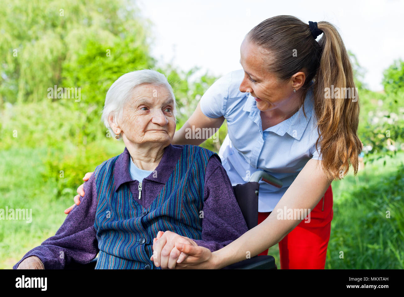 Senior invalid woman spending time outdoor with friendly young caregiver - Stock Image