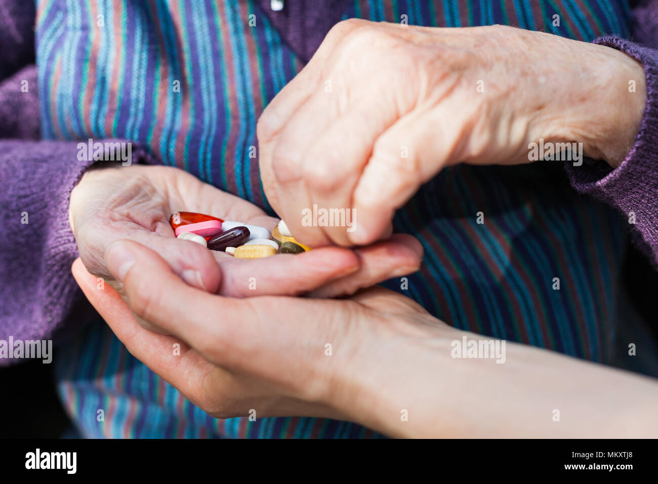 Close up picture of elderly disabled woman's hands receiving medical drugs from caregiver - Stock Image