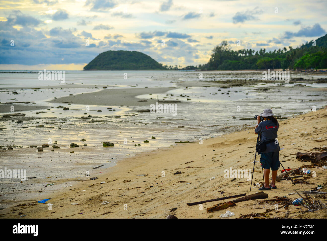 Surat Thani, Thailand - May 25, 2013: Photographer on dirty beach shooting view of sea and sky in Surat Thani, Thailand - Stock Image