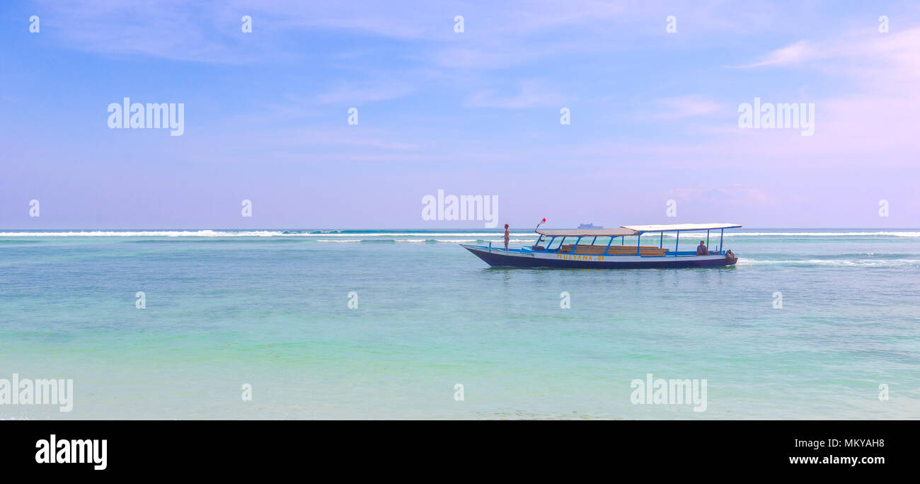seamen driving a long-tail cargo boat in the turkuoise ocean, The boat is loaded with timber and rolls in the waves, Gili Trawangan, Indonesia, april  - Stock Image