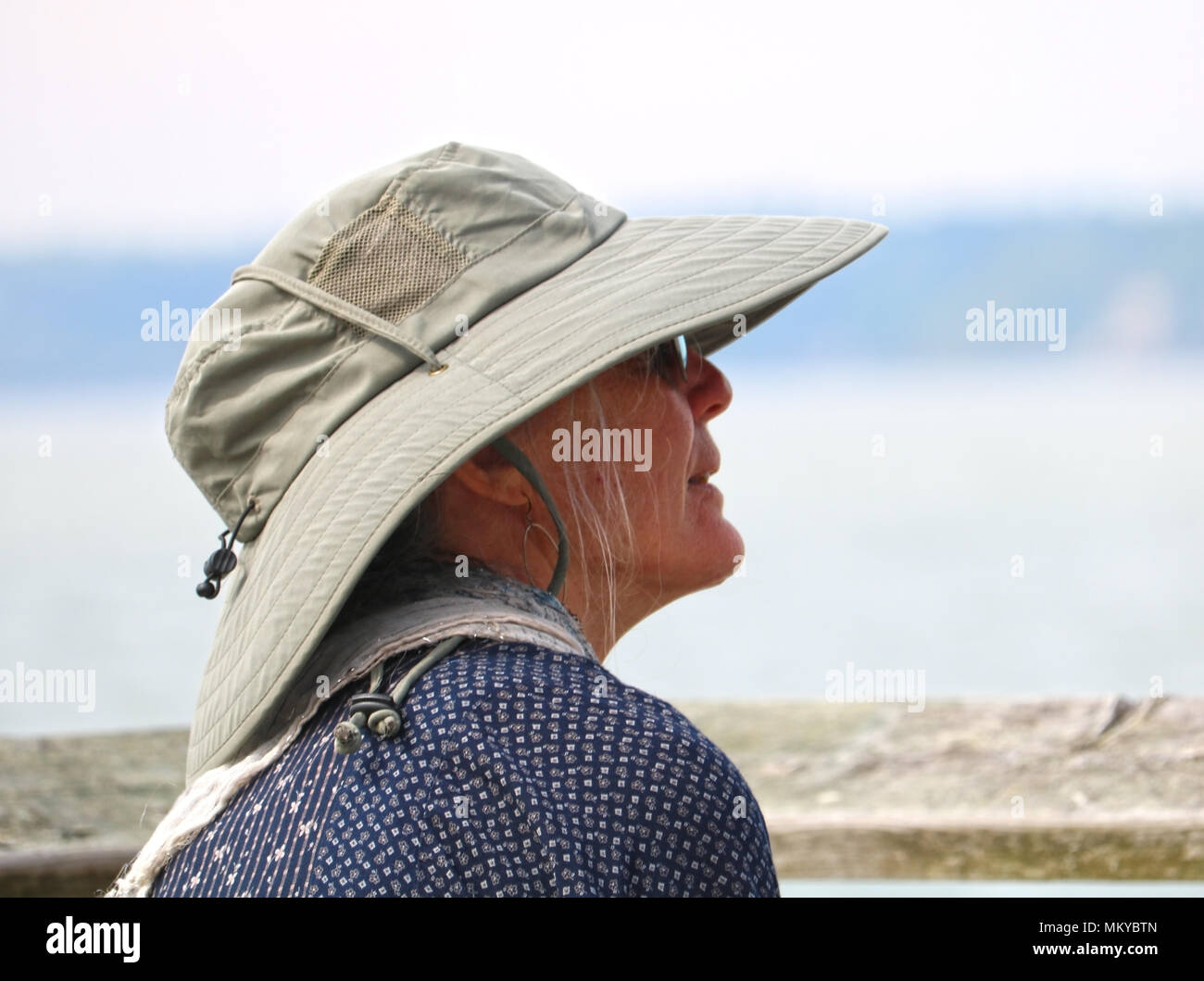 Profile of a senior woman wearing a safari style hat.  The woman is looking as if into the future, looking forward, anticipation.  A traveller. - Stock Image