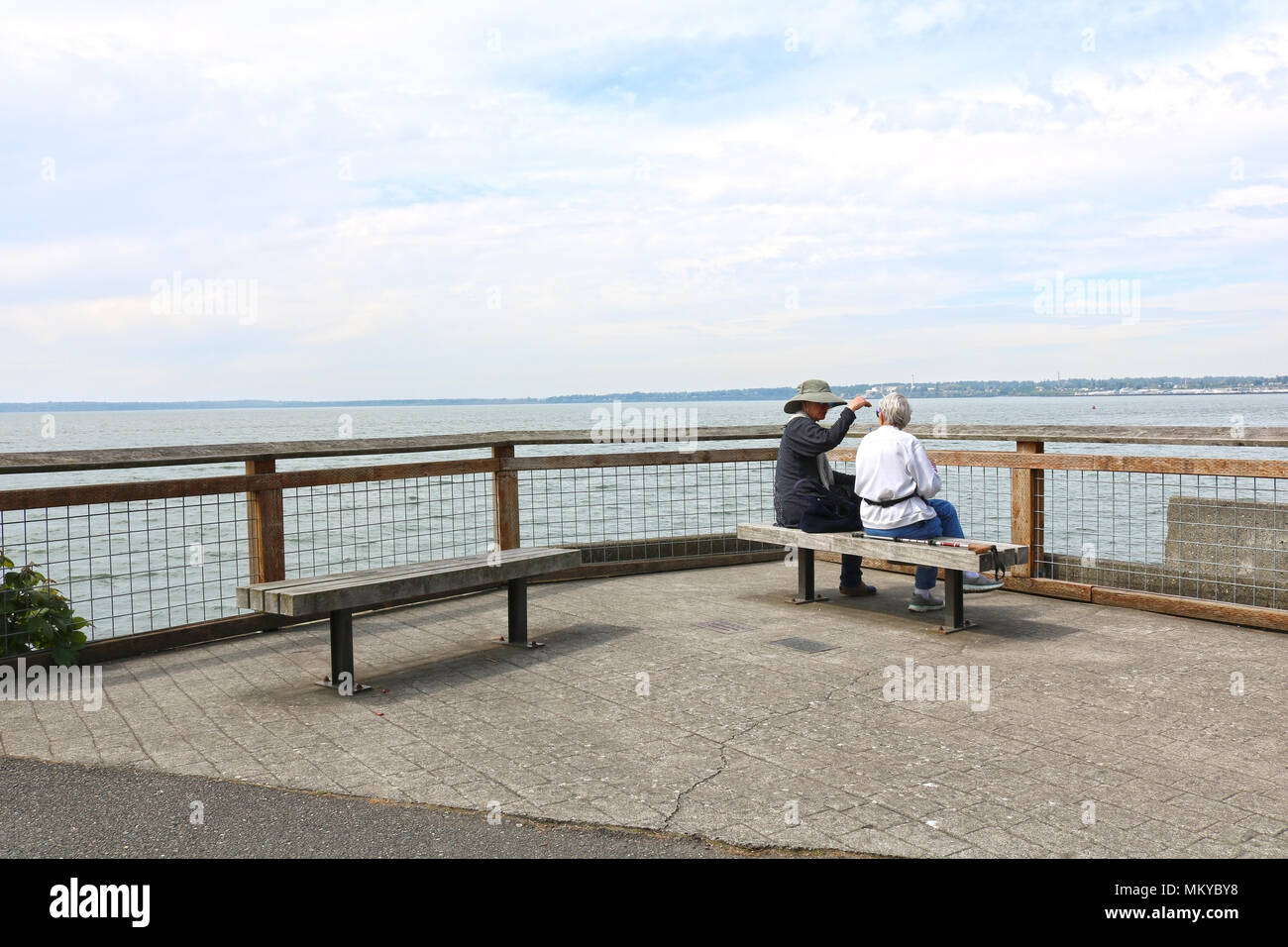 Two senior women sitting on a bench close to the railing at Boulevard Park in Bellingham, WA, USA. - Stock Image