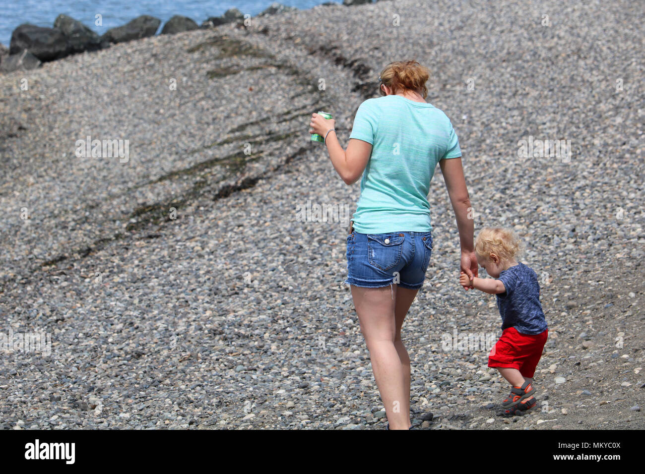 Mother holding the hand of her toddler son while they walk the beach at Boulevard Park in Bellingham, Washington, USA Stock Photo