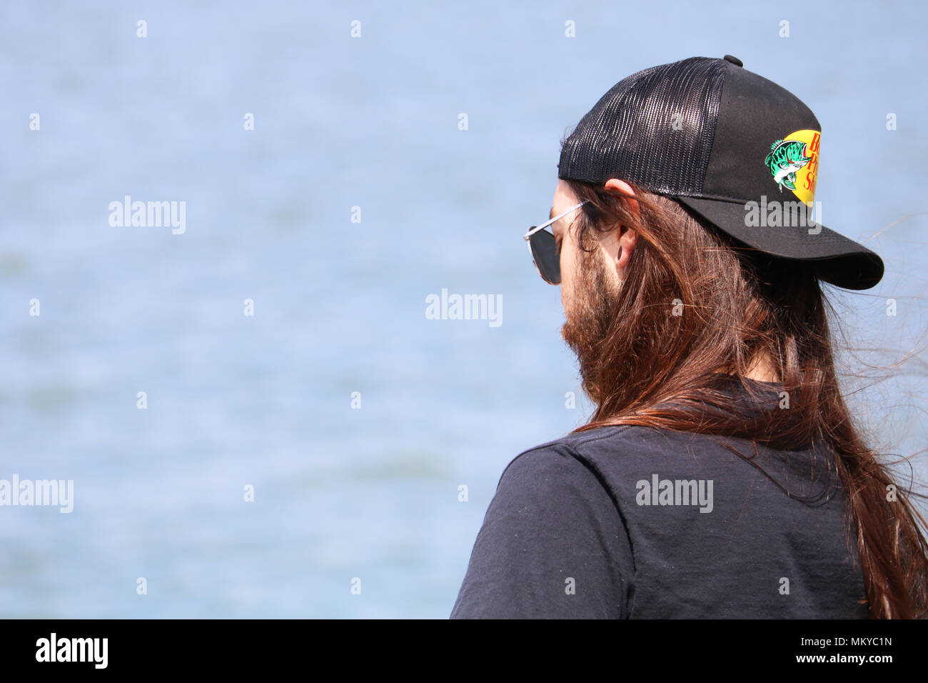 Young man with very long straight hair and beard wearing a baseball cap  from Bass Pro Shop. He is wearing the cap backwards. 1f1f88e97d3