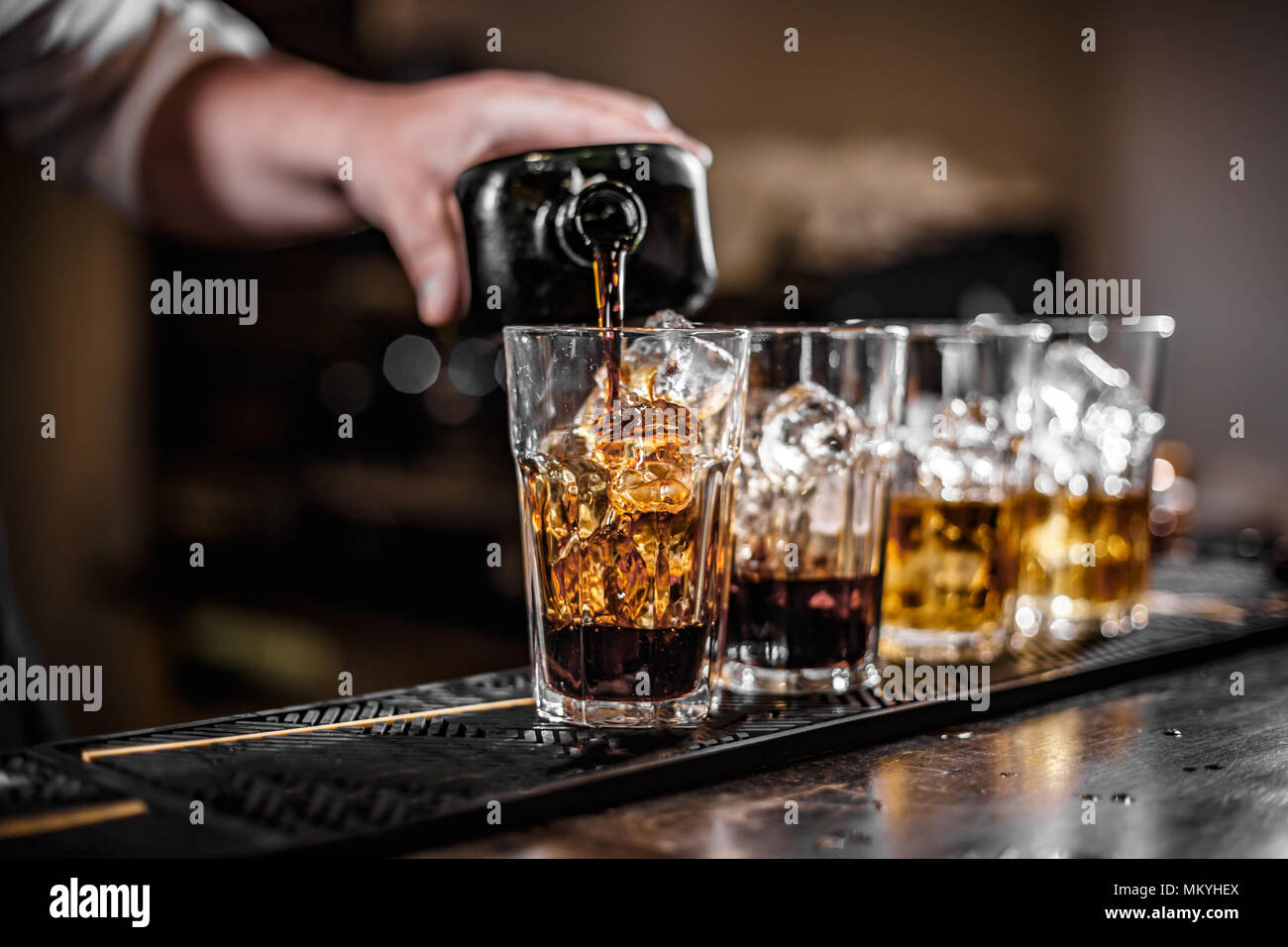 Bartender pouring alcoholic drink in glass - Stock Image