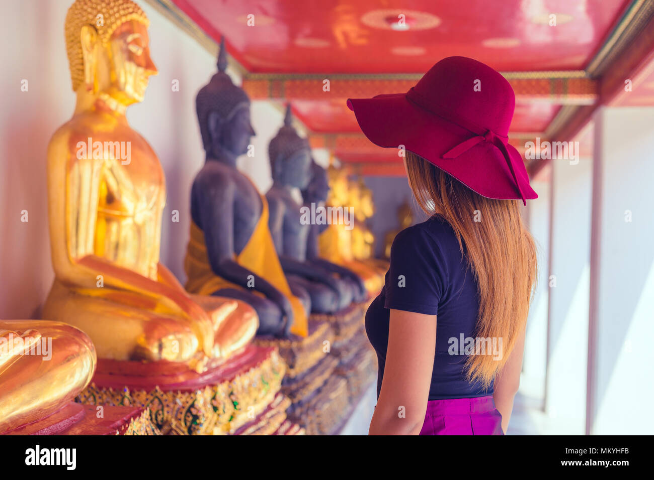 thai women with hat looking at a rows of buddhas in Wat Pho temple in Bangkok , Thailand - Stock Image