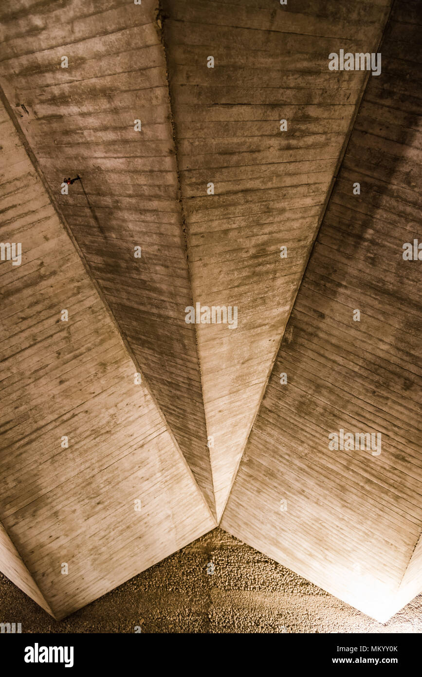 Illuminated concrete ceiling. Old textured built structure. - Stock Image