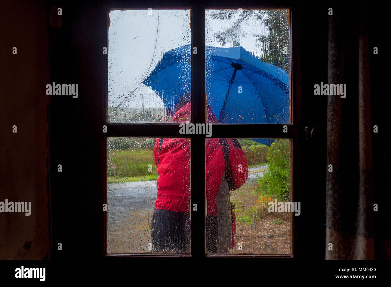 Ardara, County Donegal, Ireland  weather. 9th May 2016. A person struggles to work on a rainy, windy start to the day on Ireland's west coast. Seen through the window of a cottage. Credit: Richard Wayman/Alamy Live News Stock Photo