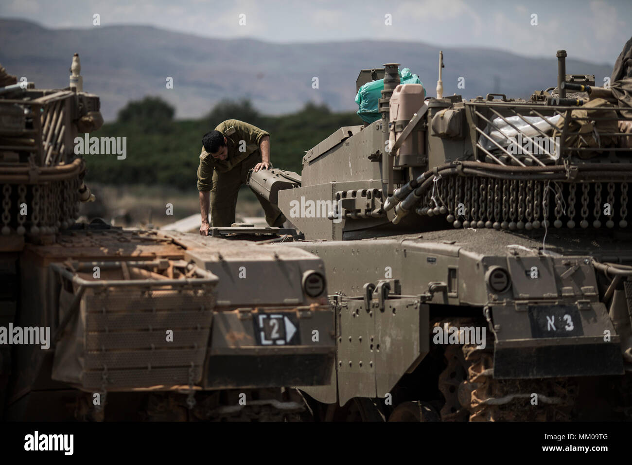 Golan Heights, Israel. 09th May, 2018. An Israeli soldier on top of a Merkava Mark IV tank that deployed along the border with Syria, in Golan Heights, Israel, 09 May 2018. Israel's army is mobilizing reservists due to concerns about a possible attacks by Iranian forces in Syria. Credit: Ilia Yefimovich/dpa/Alamy Live News - Stock Image