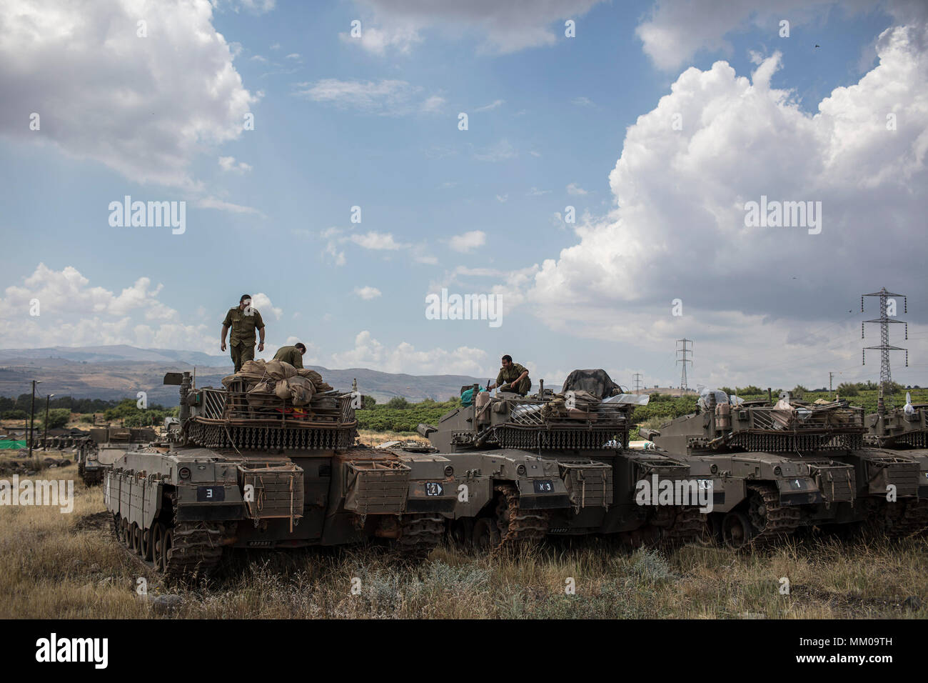 Golan Heights, Israel. 09th May, 2018. Israeli soldiers on top of a Merkava Mark IV tank that deployed along the border with Syria, in Golan Heights, Israel, 09 May 2018. Israel's army is mobilizing reservists due to concerns about a possible attacks by Iranian forces in Syria. Credit: Ilia Yefimovich/dpa/Alamy Live News - Stock Image