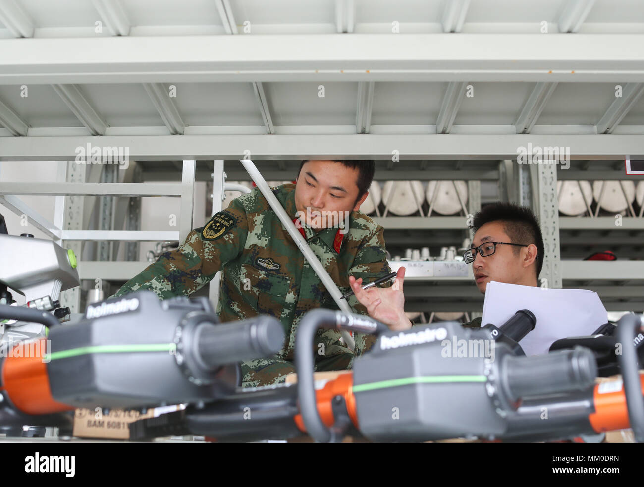 (180509) -- CHENGDU, May 9, 2018 (Xinhua) -- Fire services officer Jiang Yuhang (R) and soldier Xu Songsong check the firefighting equipment in Kaili City, southwest China's Guizhou Province, May 8, 2018. On May 17, 2008, Jiang, a 20-year-old highway administration employee, was extricated by firefighters, 123 hours after he was trapped in the rubble at quake-hit Yingxiu Township of Wenchuan County, southwest China's Sichuan Province. Jiang was a survivor of the 8.0-magnitude earthquake that struck Sichuan's Wenchuan County on May 12, 2008. The quake left more than 69,000 dead, 374,000 injur - Stock Image