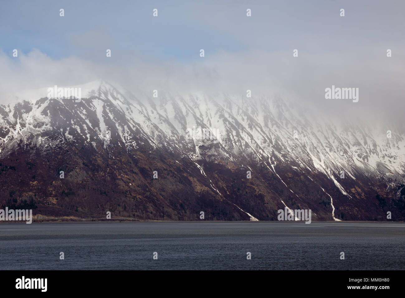 Turnagain Arm, Tidal Flats, Trees, Mountains and Water. Near Hope, Alaska. Rocky Shoreline. Snow capped Chugach Mountains. Kenai Peninsula Windy Point - Stock Image