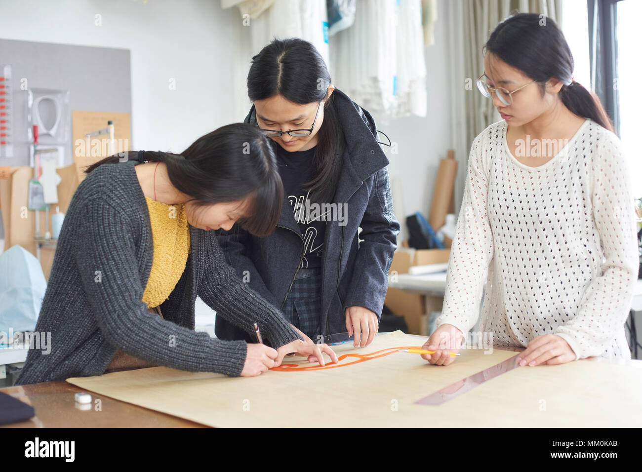 Trainee to study fashion design in the studio - Stock Image