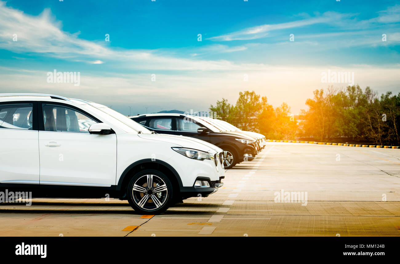 Luxury white and black new suv car parked on concrete parking area at factory with blue sky and clouds. Car stock for sale. Car factory parking lot. A - Stock Image