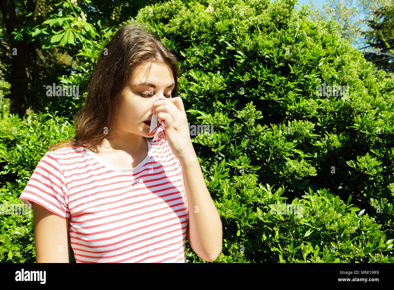 Woman with with allergy symptom blowing nose. - Stock Image
