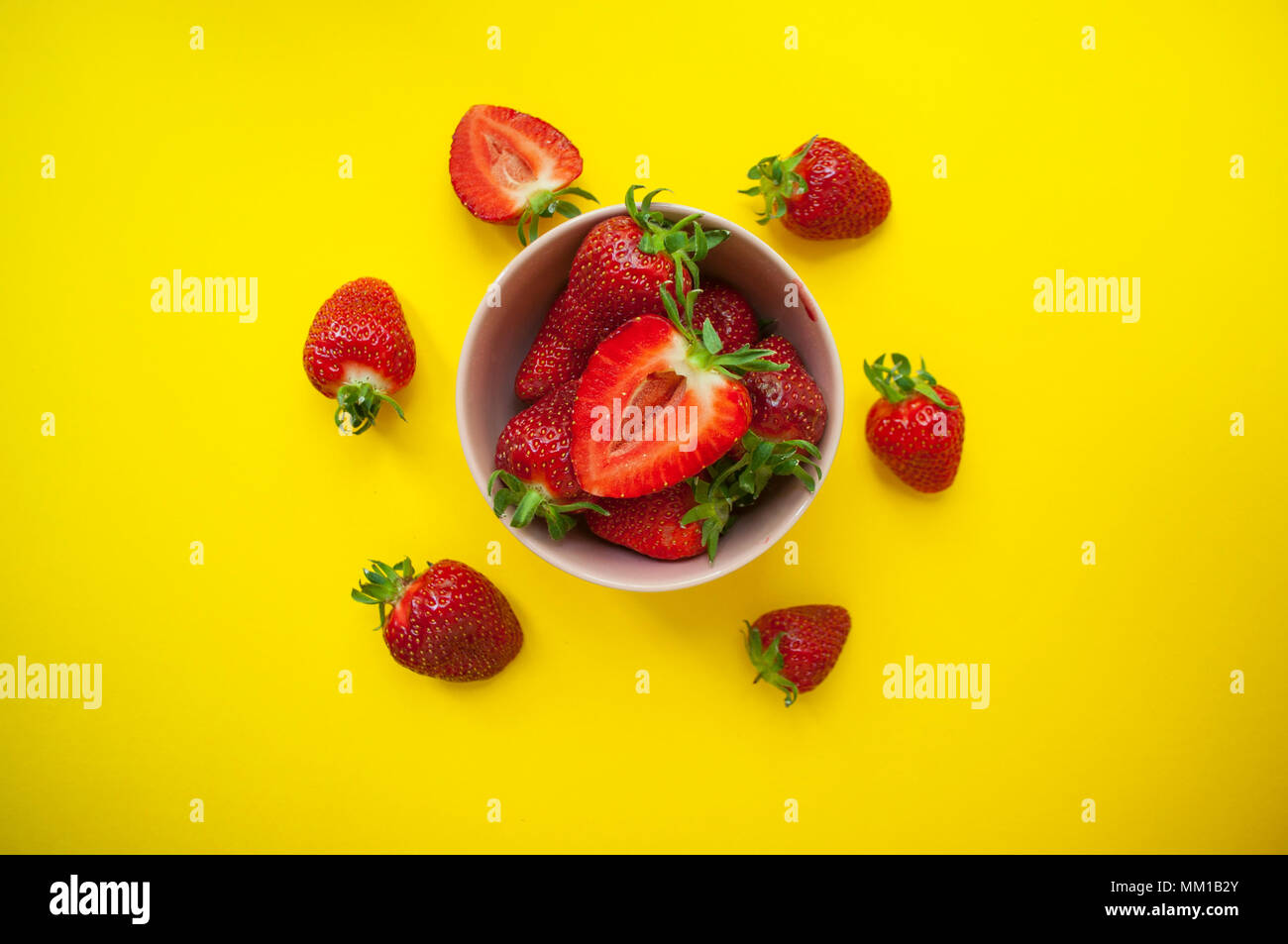 Beautiful fresh juicy strawberries in a pink bowl on bright yellow background. - Stock Image