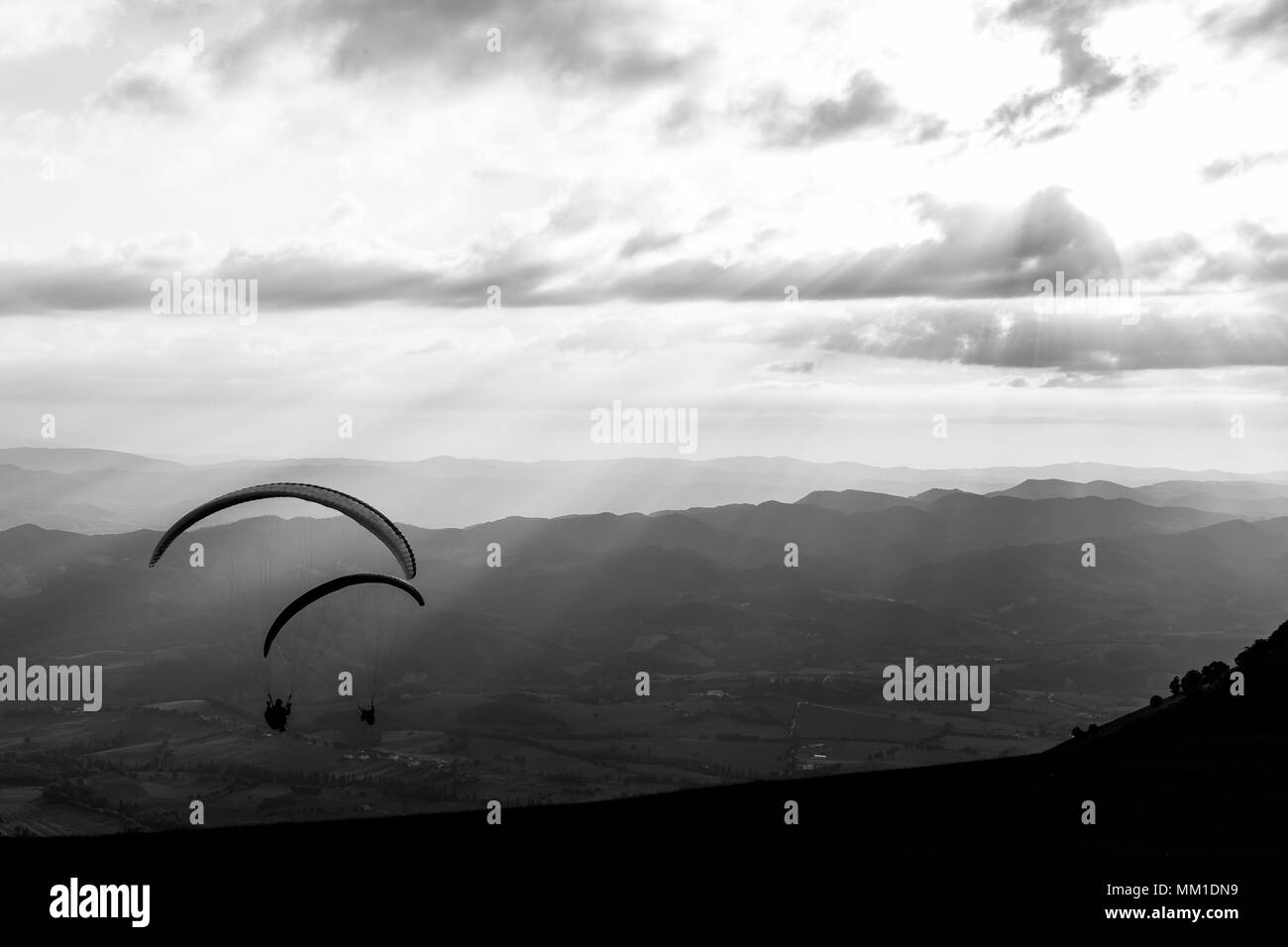 Some paragliders flying over a mountain scenery, with some faint sunrays in the background - Stock Image