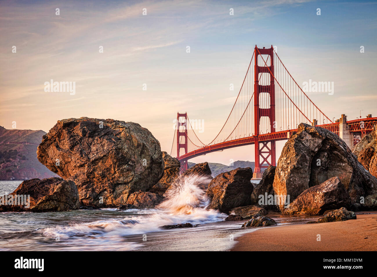 Golden Gate Bridge, San Francisco, approaching sunset., with a wave splashing up against rocks. - Stock Image