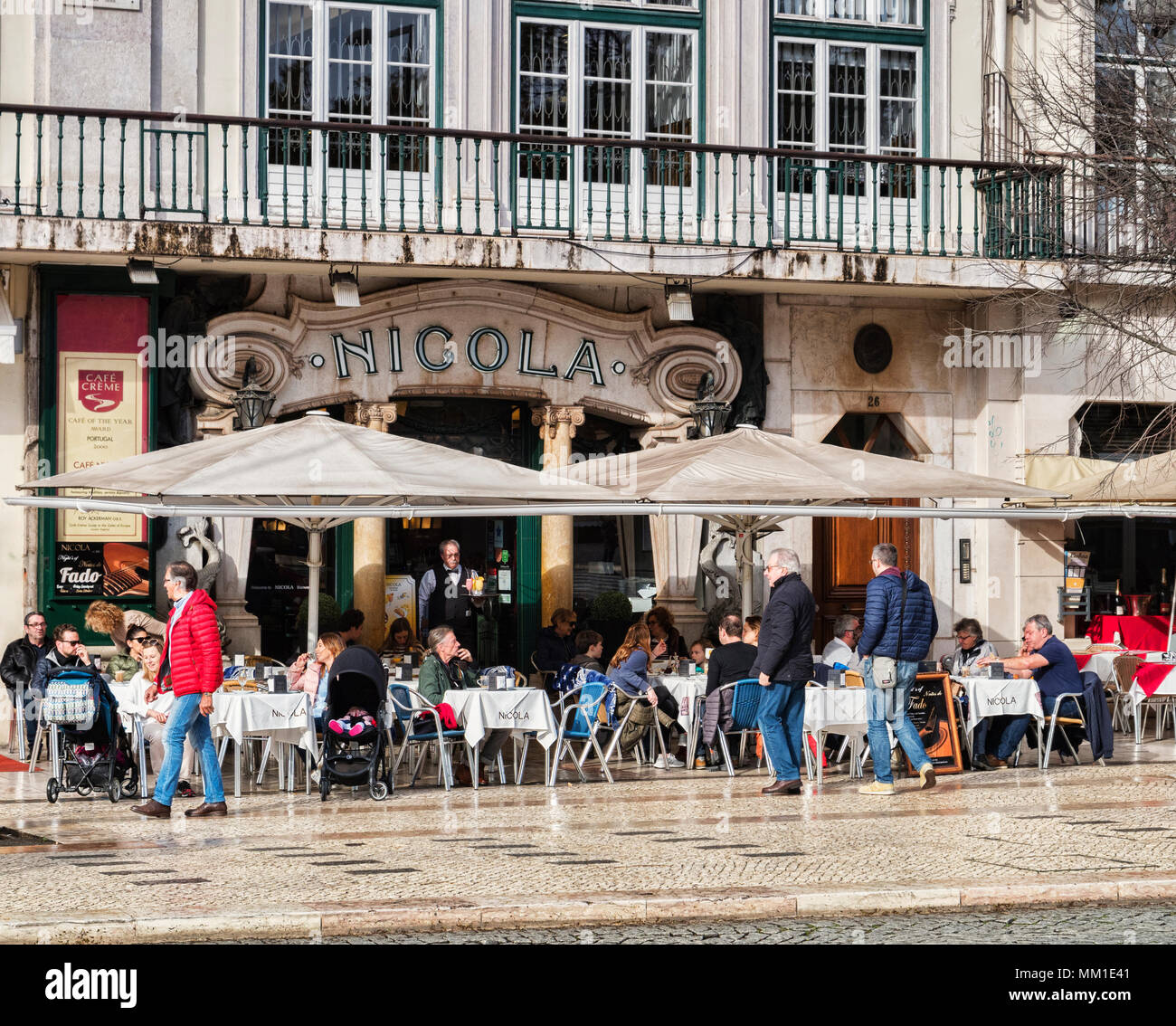 27 February 2018: Lisbon, Portugal - Cafe Nicola, Praca dom Pedro, with customers sitting outside in the winter sunshine, the art deco facade has been - Stock Image