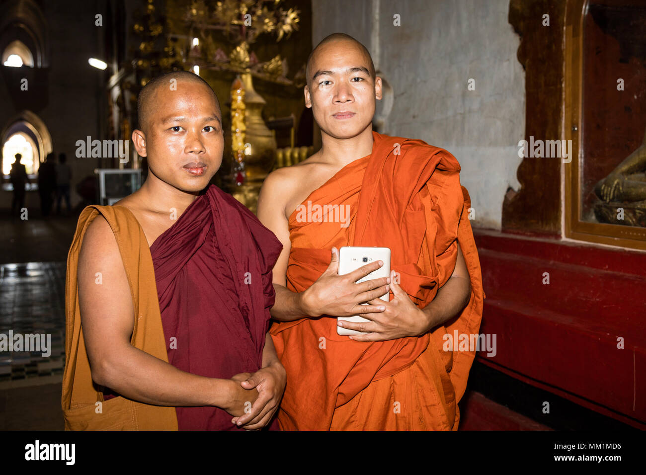 Bagan, Myanmar, December 29, 2017:  Portrait of two Buddhist monks in the Ananda Pagoda in Bagan. A monk holds a tablet in his hand. - Stock Image