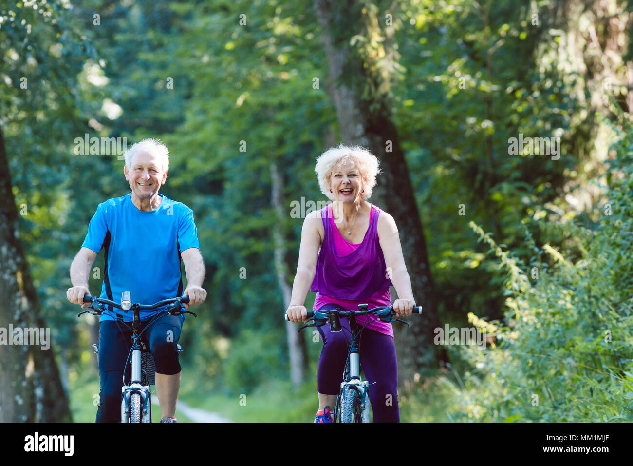 Happy and active senior couple riding bicycles outdoors in the park - Stock Image