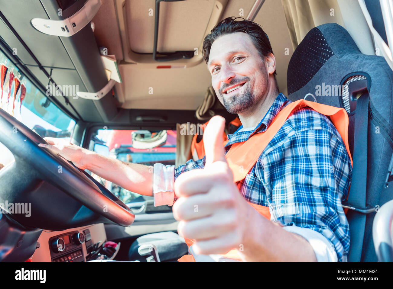 Truck driver sitting in cabin giving thumbs-up - Stock Image