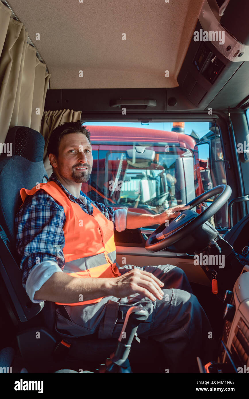 Lorry or truck driver sitting in the cabin of his vehicle - Stock Image