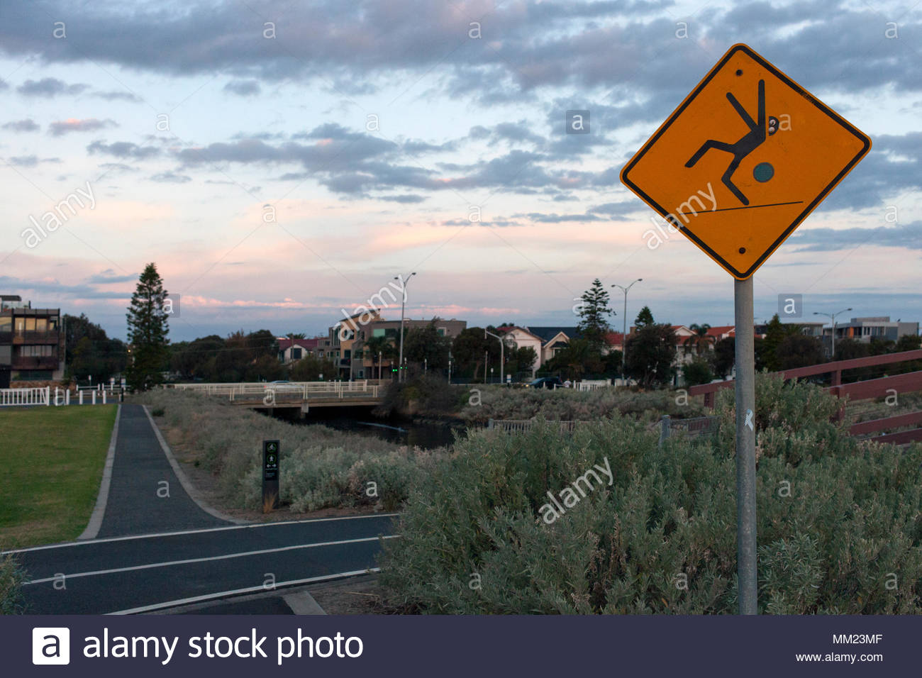 Vandalized sign - a 'caution slippery' sign now advertising a place for 'high jump'  -  in Elwood, Melbourne, Victoria on the Bay bike Trail - Stock Image