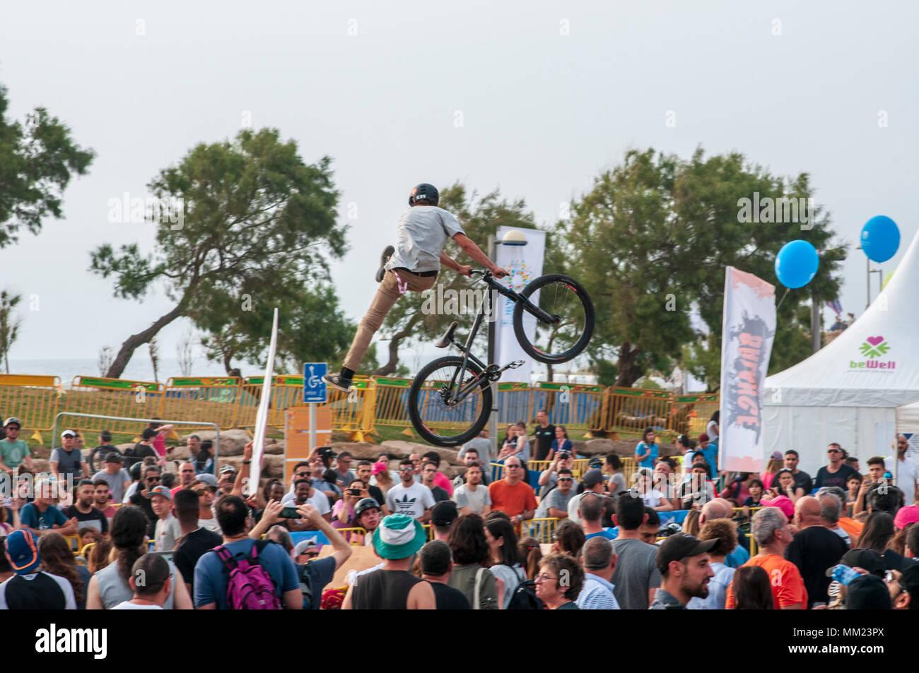 Bicycle stuntman a crowd of people watching below - Stock Image