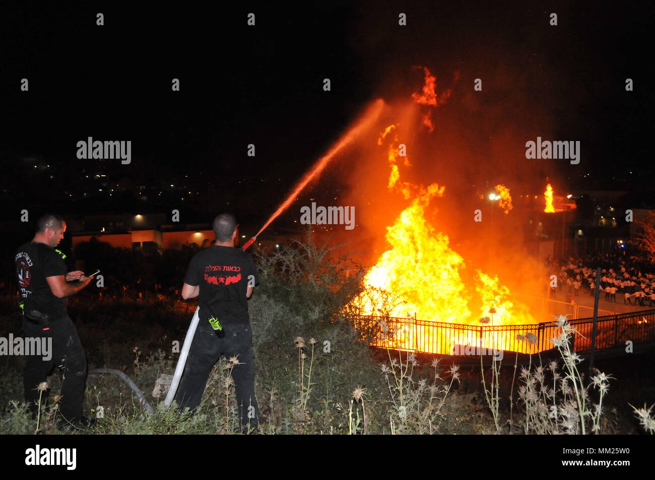 Firefighter extinguish a large bonfire during the lag b'omer celebrations (Lag B'Omer is a day for bonfire celebrations.) - Stock Image