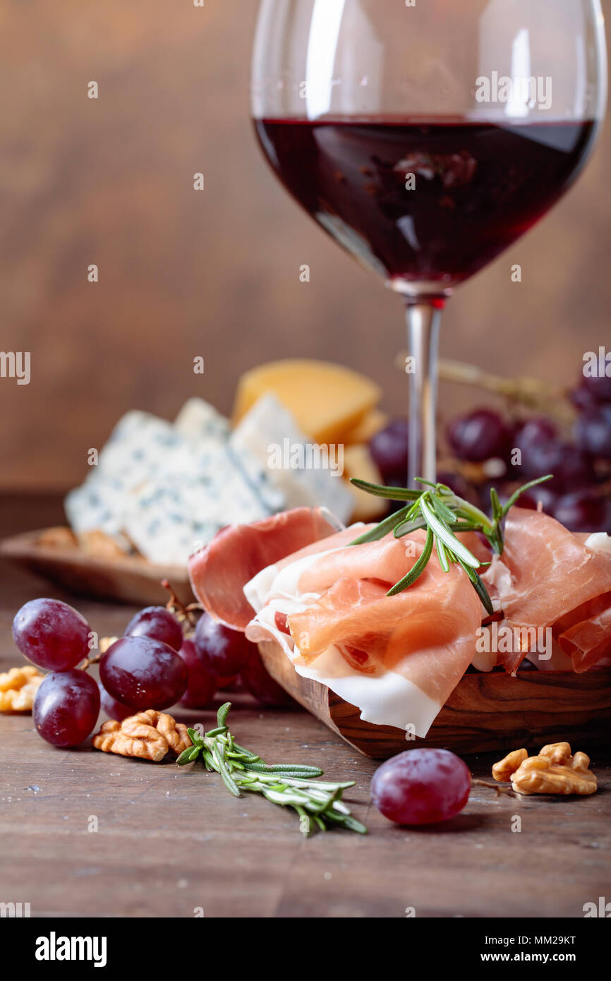 Glass of red wine with various cheeses , fruits and prosciutto on a old wooden table. - Stock Image