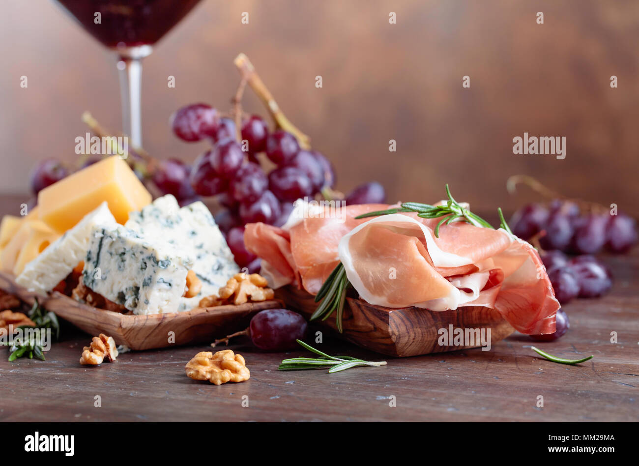Prosciutto with various cheeses , grapes and  walnuts on a old wooden table. Copy space . - Stock Image