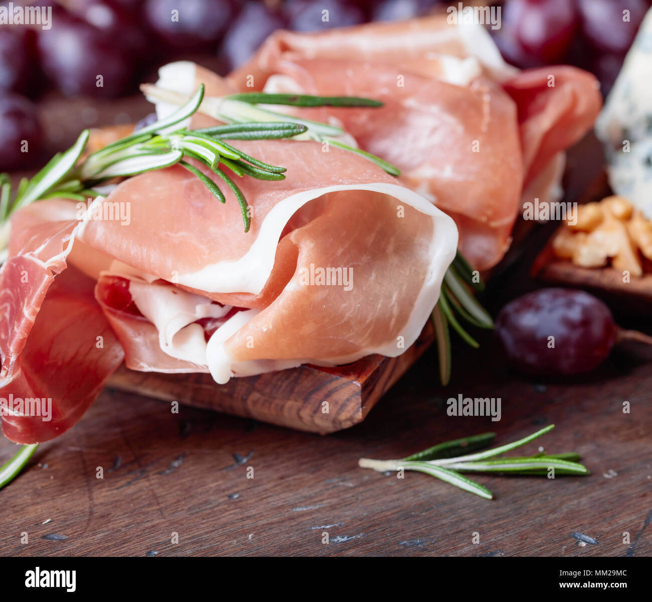 Prosciutto with grapes and rosemary on a old wooden table. - Stock Image