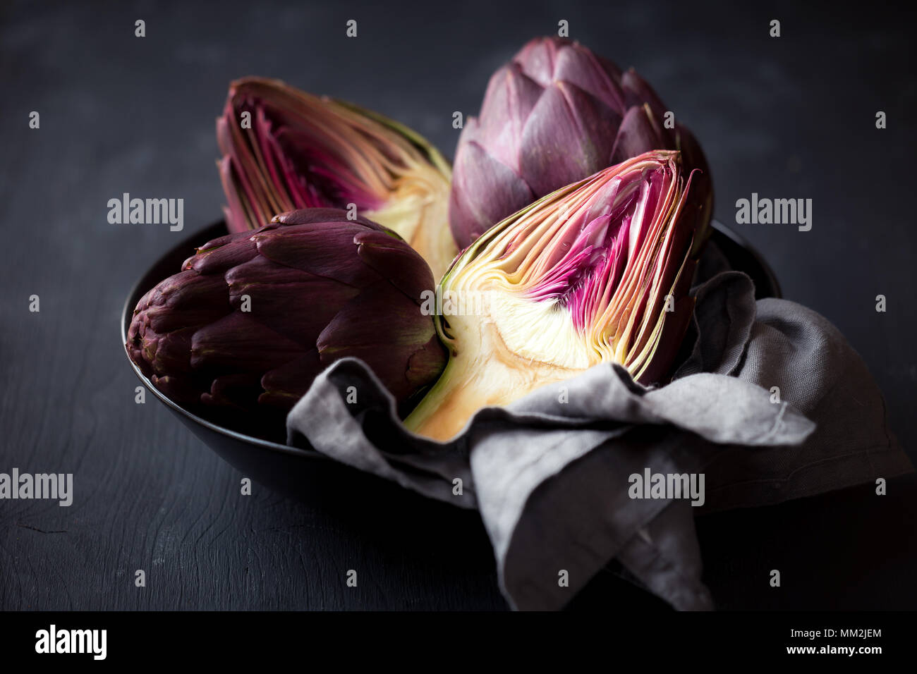 Fresh ripe artichokes in a bowl against black wooden background - Stock Image