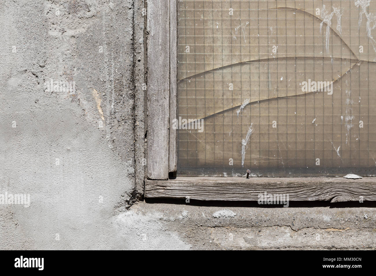 Concrete wall, wood-framed window with cracked wire mesh glass; Copenhagen Harbor, Denmark - Stock Image