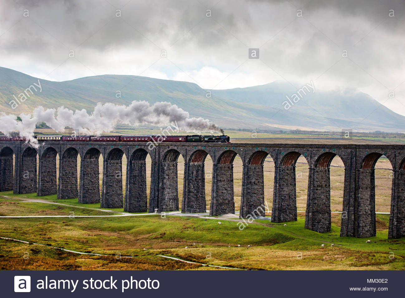 35018 SR Merchant Navy Class British India Line steam engine crosses Ribblehead Viaduct in the Yorkshire Dales. - Stock Image