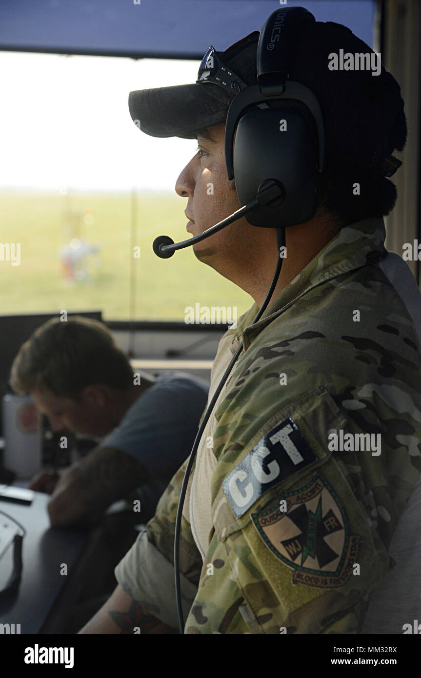 Tech. Sgt. Daniel, 350 Battlefield Airman Training Squadron combat controller, communicates with helicopters crossing at JBSA Randolph auxiliary airfield, Seguin, Texas, Sept 1, 2017. Daniel is supporting FEMA disaster-relief efforts for a category-4 hurricane with 130 mph winds as it made landfall, August 25, 2017.  Days after the hurricane reached the Texas, more than 50 inches of rain flooded the coastal region. (U.S. Air Force Photo by Tech. Sgt. Chad Chisholm/Released) Stock Photo