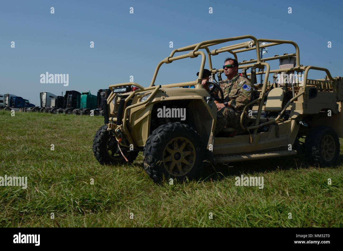 Tech Sgt. Justin, 350 Battlefield Airman Training Squadron combat controller, and Staff Sgt. Mason, 350 Battlefield Airman Training Squadron Pararescueman, depart in a Light Tactical All terrain Vehicle (LTATV) to clear an active runway of unauthorized access at JBSA Randolph auxiliary airfield, Seguin, Texas, Sept. 1, 2017. Justin and Mason are supporting FEMA's disaster-relief efforts after hurricane Harvey, a category-4 hurricane with 130 mph winds as it made landfall, Aug. 25, 2017, caused more than 50 inches of rain and flooding in the coastal regions. (U.S. Air Force Photo by Tech. Sgt.  Stock Photo