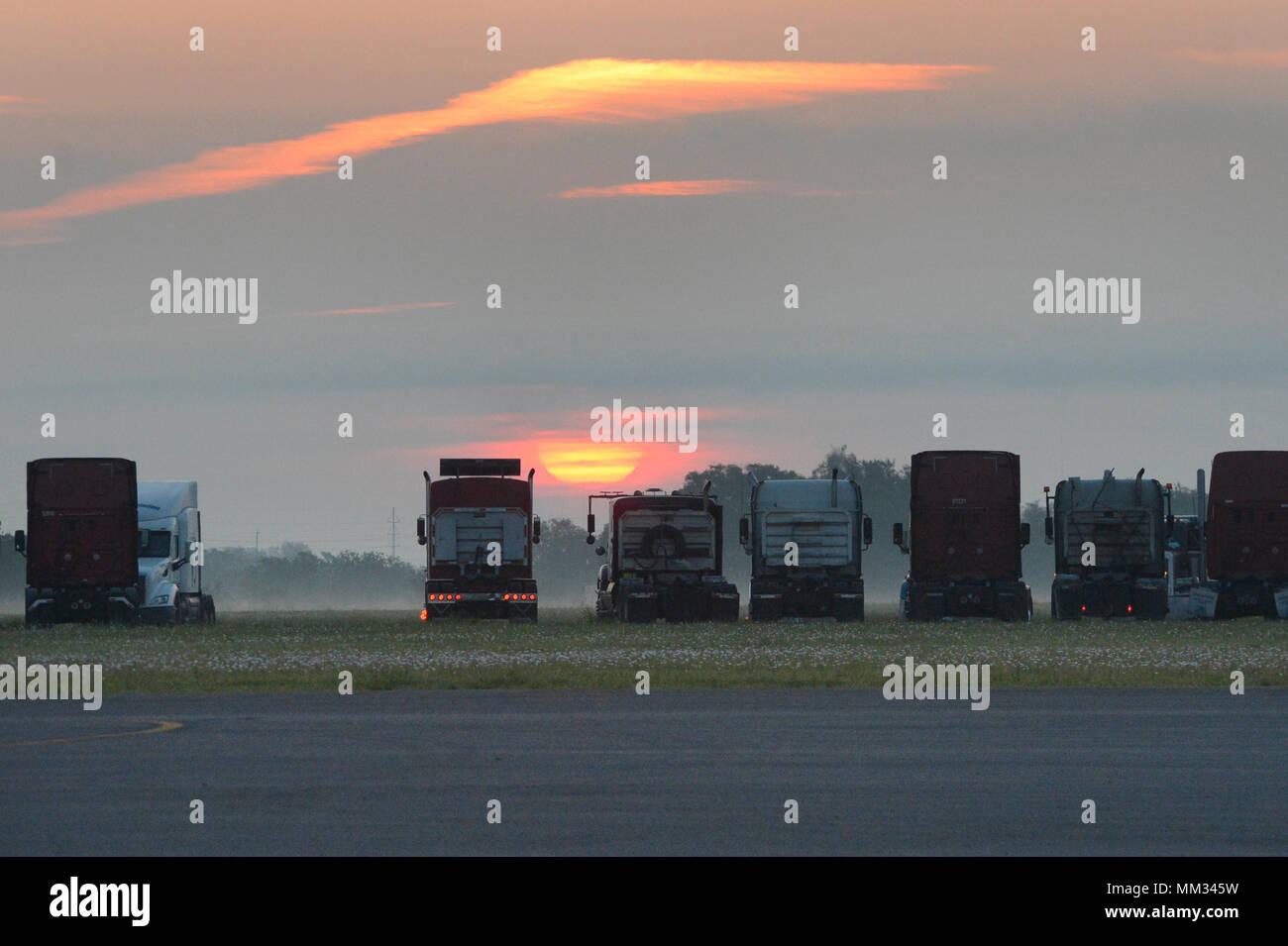 The sun rises over diesel trucks at JBSA Randolph auxiliary airfield, Seguin, Texas, September 1, 2017. The trucks are supporting disaster-relief efforts for a category-4 hurricane with 130 mph winds as it made landfall, August 25, 2017.  Days after the hurricane reached the Texas, more than 50 inches of rain flooded the coastal region. (U.S. Air Force Photo by Tech. Sgt. Chad Chisholm/Released) Stock Photo