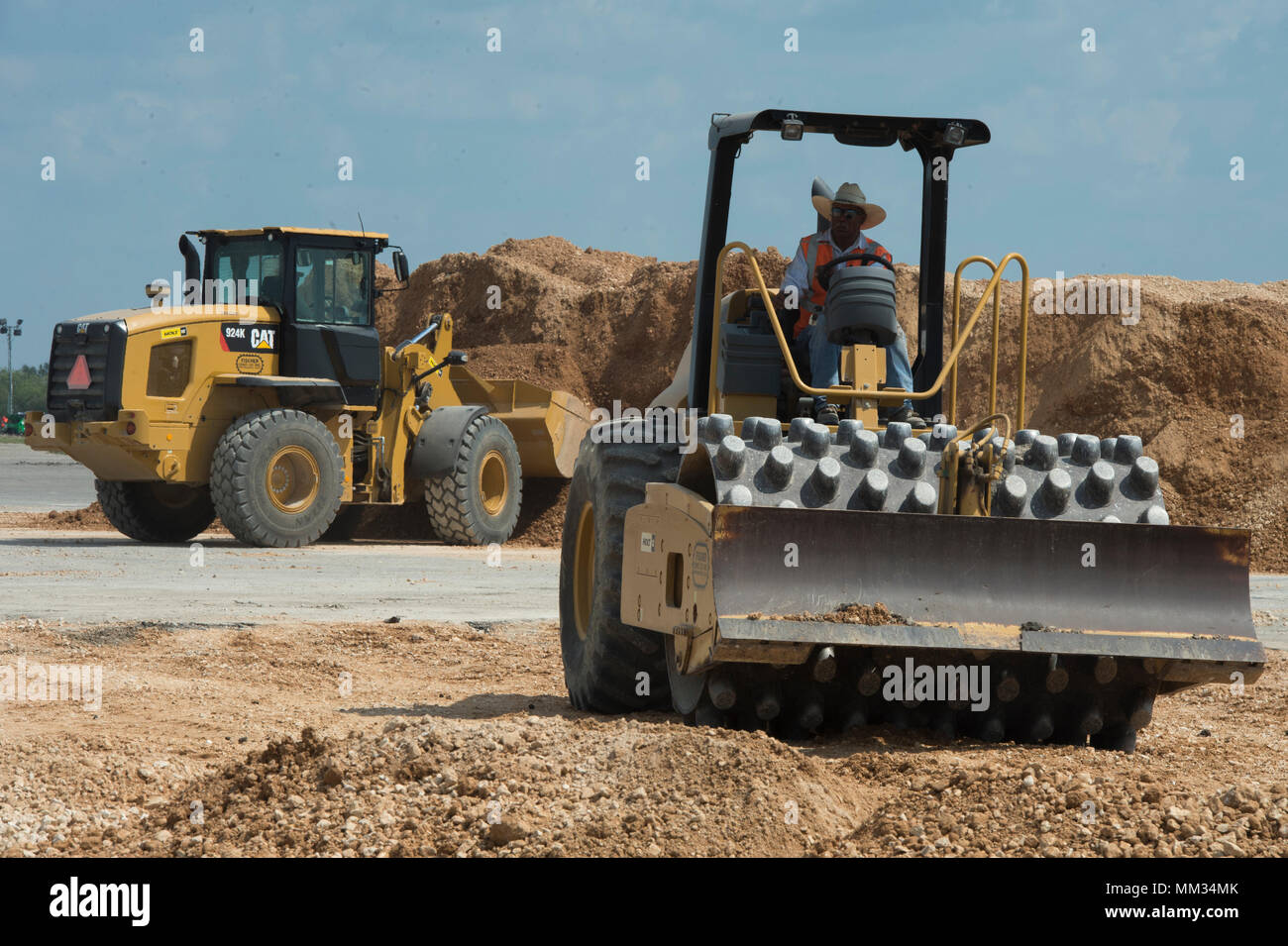 Fischer Construction Company, contractors,  use a vibratory soil compactor  and a wheel loader to create a new entry point at JBSA Randolph auxiliary airfield, Seguin, Texas, 2 September, 2017.  The New Braunfels, Texas  company is helping increase the storage area for Hurricane Harvey relief trailers supporting disaster-relief efforts for the category-4 hurricane with 130 mph winds as it made landfall, August 25, 2017.  Days after the hurricane reached the Texas, more than 50 inches of rain flooded the coastal region. (U.S. Air Force Photo by Tech. Sgt. Chad Chisholm/Released) Stock Photo