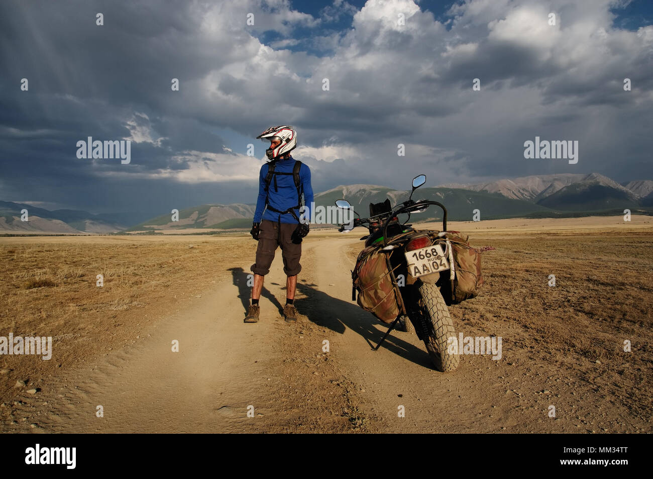 Motorcycle traveler man in helmet with suitcases standing on extreme rocky road in a mountain valley in cloudy weather on the background of endless st Stock Photo