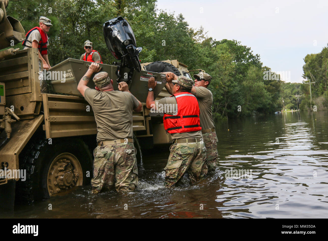 Texas National Guardsmen unload a boat off of a Light Medium Tactical Vehicle (LMTV) to traverse high water through flooded neighborhoods in Vidor, Texas, Sept. 3, 2017. The boats were used when the LMTVs were not able to pass through certain areas. The Guardsmen continue to provide relief to those who were affected by Hurricane Harvey. The Department of Defense is conducting Defense Support of Civil Authorities operations in response to the effects of Hurricane Harvey. DSCA operations are part of the DOD's response capability to assist civilian responders in saving lives, relieving human suff - Stock Image