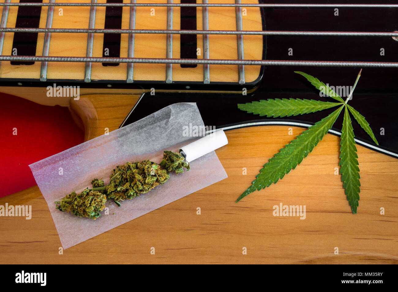 Joint ready to roll and marijuana leaf on vintage electric bass of four strings. Musical instrument and drugs, concept of look for inspiration. - Stock Image