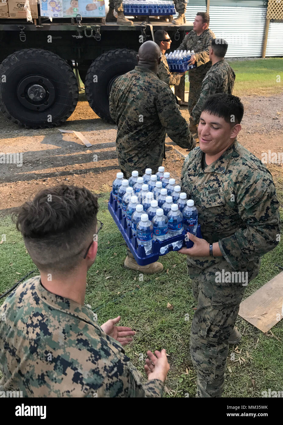 BEAUMONT, Texas - U.S. Marines from 14th Marine Regiment, 4th Marine Division, Marine Forces Reserve, Marine Wing Support Squadron 473, 4th Marine Aircraft Wing, MARFORRES, unload pallets of water from an MTVR 7-ton truck at Rosehill Acres, Texas, Sept. 3, 2017.  14th Marines, based out of Ft. Worth, Texas, is participating in relief efforts for those effected by Hurricane Harvey. (U.S. Marine Corps photo by Master Sgt. Ricardo Morales/Released) - Stock Image